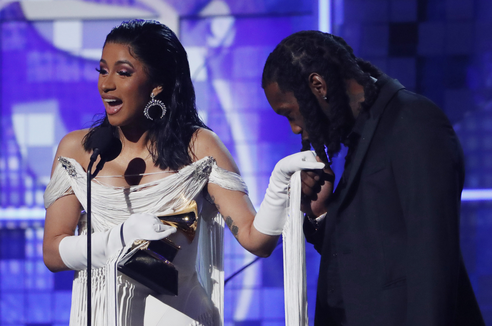 "61st Grammy Awards - Show - Los Angeles, California, U.S., February 10, 2019 - Cardi B accepts the Best Rap Album award for ""Invasion of Privacy"" as her husband Offset kisses her hand. REUTERS/Mike Blake"